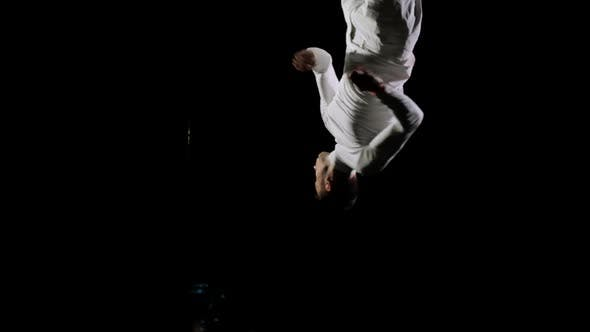 Thumbnail for Handsome Male Professional Gymnast in White Clothes on a Black Background Performs at the Gymnastics