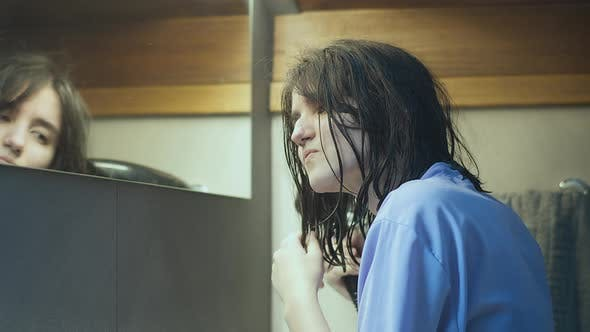 Teen Girl Dries Her Hair with a Hairdryer After a Shower