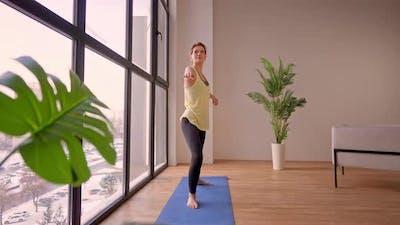 Female in Sportswear Stretching in Flat