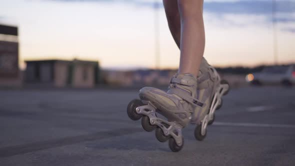 Slim Female Legs in Roller Skates Riding at Dusk on Empty Parking Lot. Unrecognizable Young