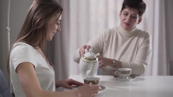 Thumbnail for Side View of Young Caucasian Girl Sitting at the Table As Her Good-looking Mother Pouring Tea Into