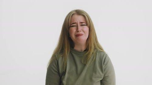 Emotional Woman in Green Sweatshirt Cries Looking in Camera