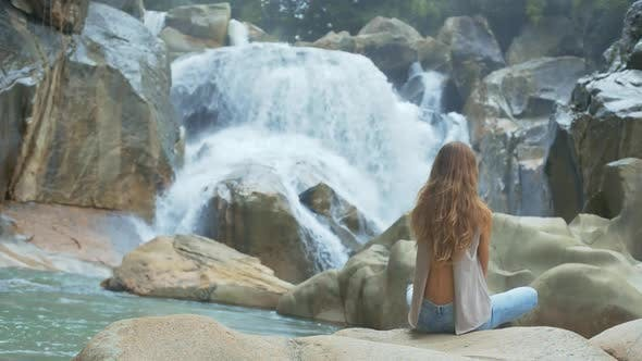 Cover Image for Girl Sits in Lotus Pose Against Waterfall and Rocks