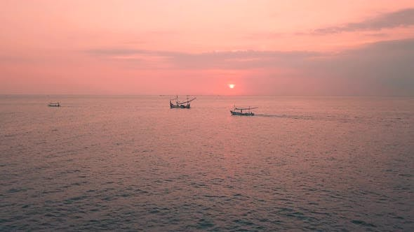 Pink Sunset Above the Sea Surface with Balinese Traditional Boats