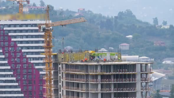 Cover Image for Building Construction. Timelapse. Tower Crane on a Construction Site Lifts a Load. Builders Work
