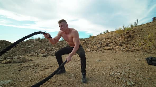 Thumbnail for Athlete doing battle rope workout. Muscular young man working out with battling ropes