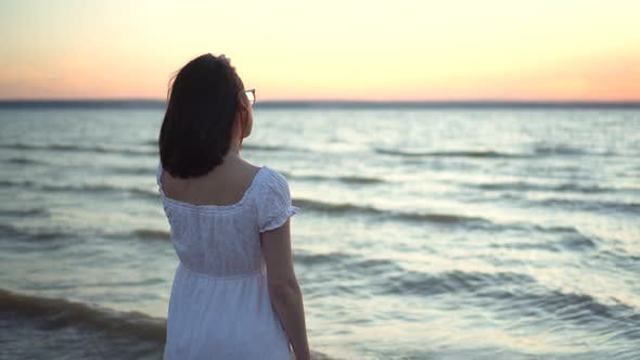 Thumbnail for Attractive Young Woman Looks at the Sunset on the Beach By the Sea. The Girl in a White Dress Stands