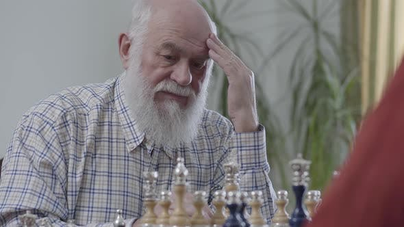 Thumbnail for Old Friends Playing Chess Sitting at Home on the Leather Sofa. Bearded Man Thinking Which Chess