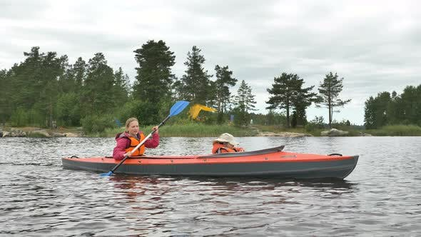 Thumbnail for Mother Rows Kayak with Girl Sailing Along Lake Near Forest