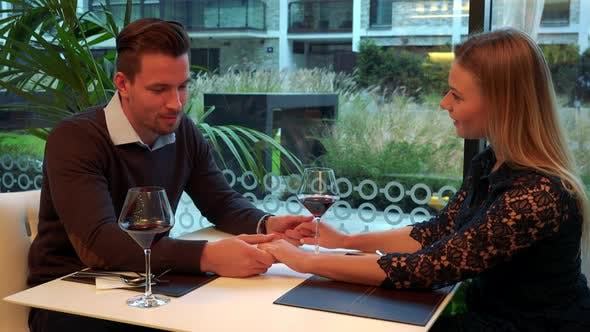 Thumbnail for A Man and a Woman Sit at a Table in a Restaurant, Talk and Hold Hands