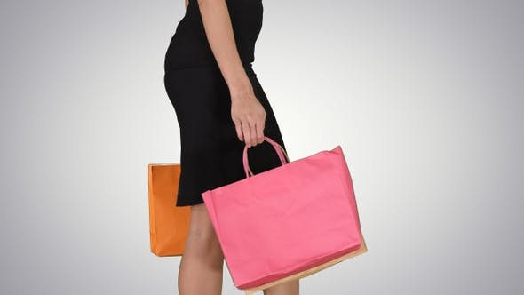 Cover Image for Young woman with shopping bags walking out from shop on