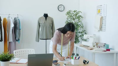 Pretty Asian Girl Fashion Designer is Drawing Fashionable Clothes on Paper Creating New Collection