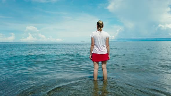 Thumbnail for A Woman Is Standing in the Sea Against the Blue Sky