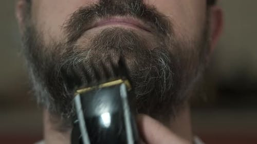 A woman cuts her husband's beard with an electric clipper in the kitchen during quarantine.