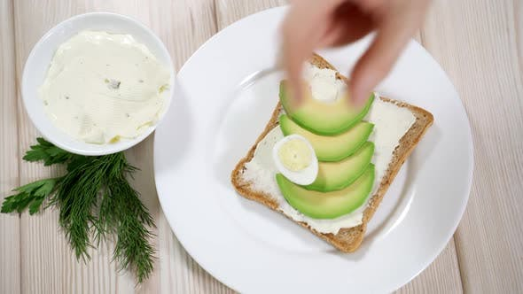Thumbnail for Woman Preparing a Healthy Breakfast - Toast with Curd Cheese and Avocado, Quail Eggs