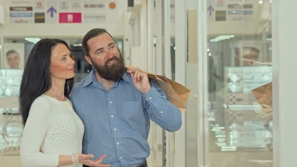Thumbnail for Happy Mature Couple Looking at Clothing Store Showcase at the Shopping Mall