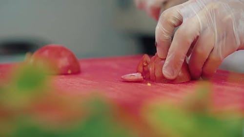 Cook Cuts a Fresh Tomato for a Salad with a Knife