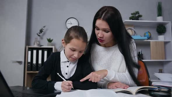 Thumbnail for Brunette Woman which Controling How Her 10-aged Cute Daughter Doing Hometask
