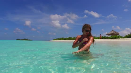 Beautiful fun women on vacation spending quality time at the beach on paradise white sand and blue