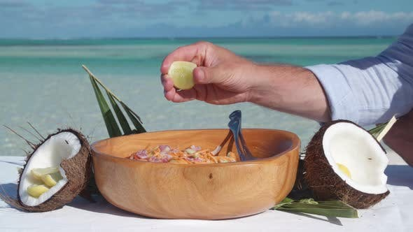 Thumbnail for A man squeezing lemon on a poke salad lunch in a bowl.