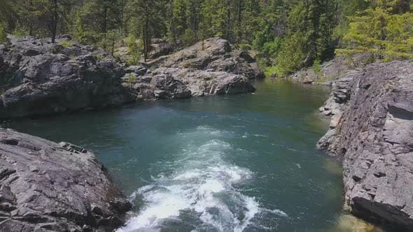 Thumbnail for Aerial Drone Traveling Above Flowing Water With Small Rocky Island Below 4