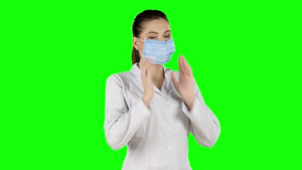 Cover Image for Young Attractive Woman Putting on Health Mask. Green Screen