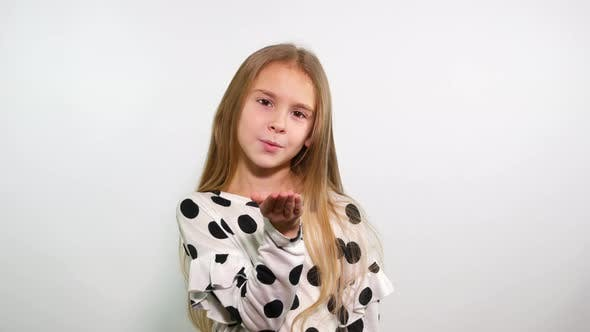 Thumbnail for Smiling Young Girl in White Top with Black Dots Sends Air Kiss at the Camera