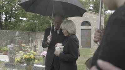 Mourners standing at funeral with cremation urn
