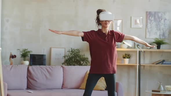 Young Woman in VR Headset Exercising at Home