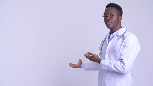 Thumbnail for Young Happy African Man Doctor Showing Something To the Back