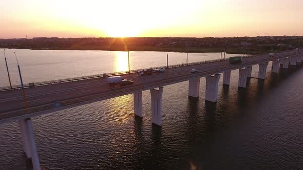 Cover Image for Aerial Shot of a Straight Bridge Over the Dnipro at Golden Sunset in Summer