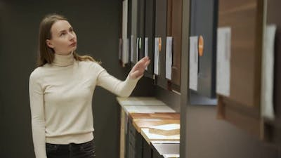 Young Woman in Shop Choosing Material for Facades for Kitchen Furniture