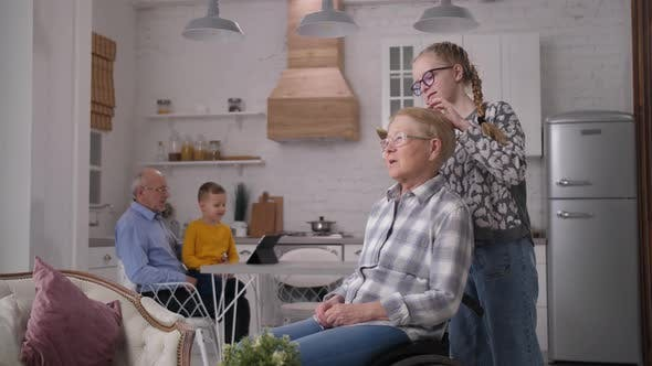 Caring Granddaughter Combing Disabled Grandmother