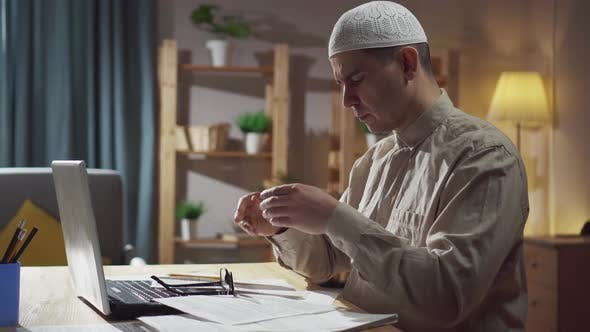 An Agitated Muslim in Skullcap Sits in the Living Room at a Laptop and Counts Finances Money Problem