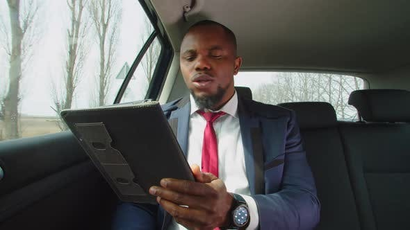 Busy Black Entrepreneur Talking on Video Chat in Vehicle