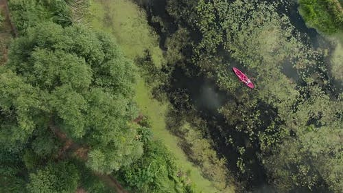 Adventure Activity. Water sports. Red boat or kayak floating on green river top view