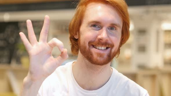 Thumbnail for Portrait of Redhead Beard Man Gesturing Okay Sign in Cafe