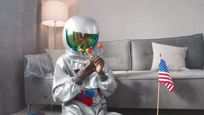 African Man in an Astronaut Costume Sitting on the Floor in Living Room at Home and Playing with a