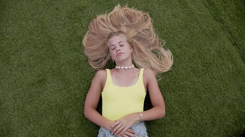 Shot of Woman Lying Down on Green Grass and Smiles