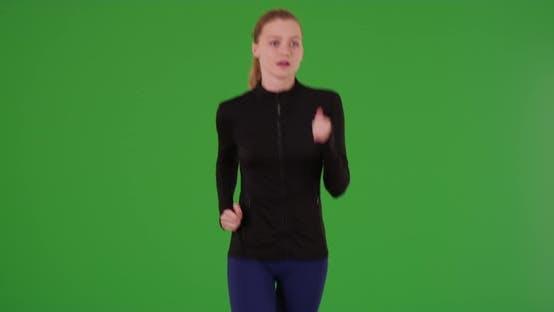 Millennial Caucasian runner looking around as she runs toward the camera