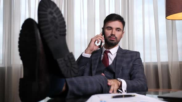 Confident Man Talking on Phone with Feet on Table