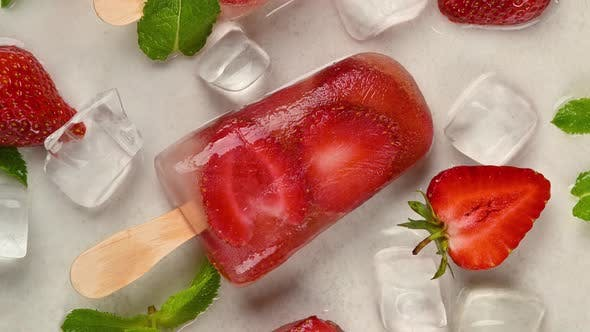 Thumbnail for Fruit ice cream popsicles with fresh strawberry, green mint leaves and ice cubes rotating