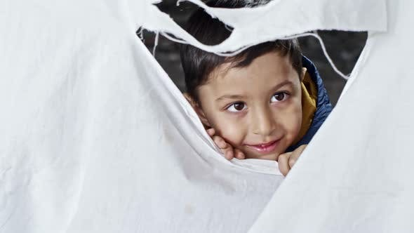 Thumbnail for Refugee Boy Laughing behind Torn Cloth