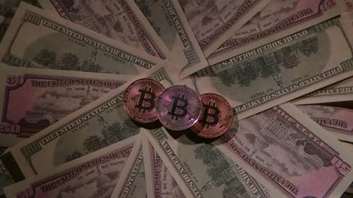 Bitcoin of Different Coins Lies on a Table on Paper Bills