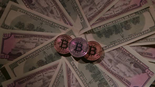 Thumbnail for Bitcoin of Different Coins Lies on a Table on Paper Bills