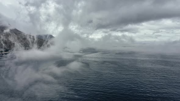 Thumbnail for Fog Covering the Frame Filled with Ocean Waters and Mountain in Slowmo