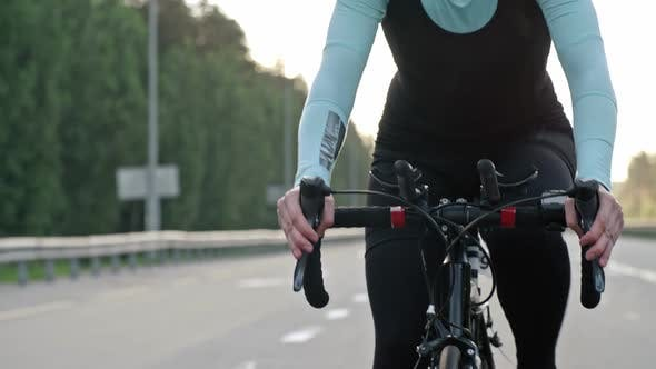 Sportswoman Cycling along Freeway