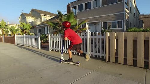 A boy rides a scooter in a neighborhood.