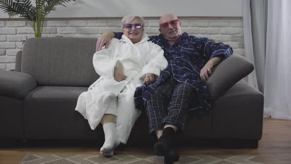 Thumbnail for Caucasian Retirees Putting on 3D Eyeglasses and Watching Movie. Joyful Positive Husband and Wife