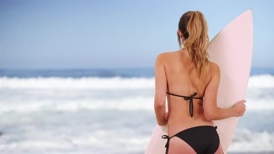Fit surfer girl shown from behind posing with surfboard by the waves in summer